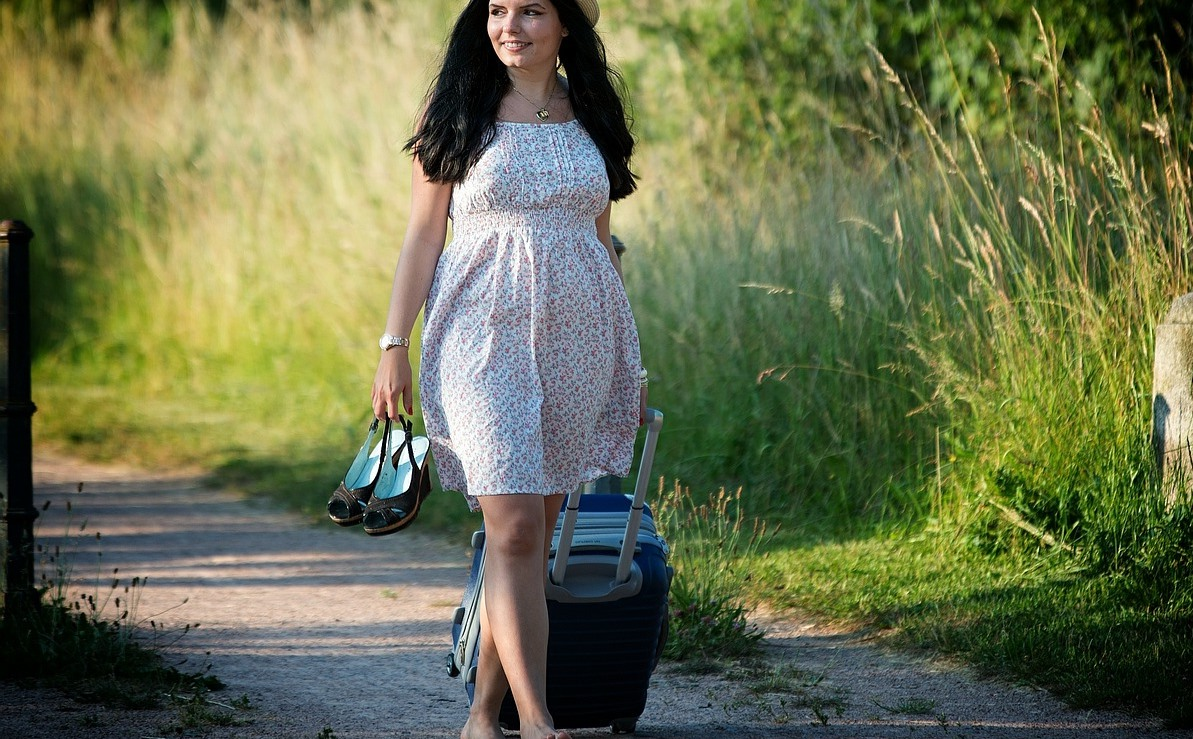 girl walking with barefoot and a luggage